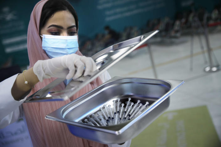A Saudi health worker carries a tray of Pfizer coronavirus vaccines, at a vaccination center in the old Jiddah airport, Saudi Arabia, Tuesday, May 18, 2021. (AP Photo/Amr Nabil)