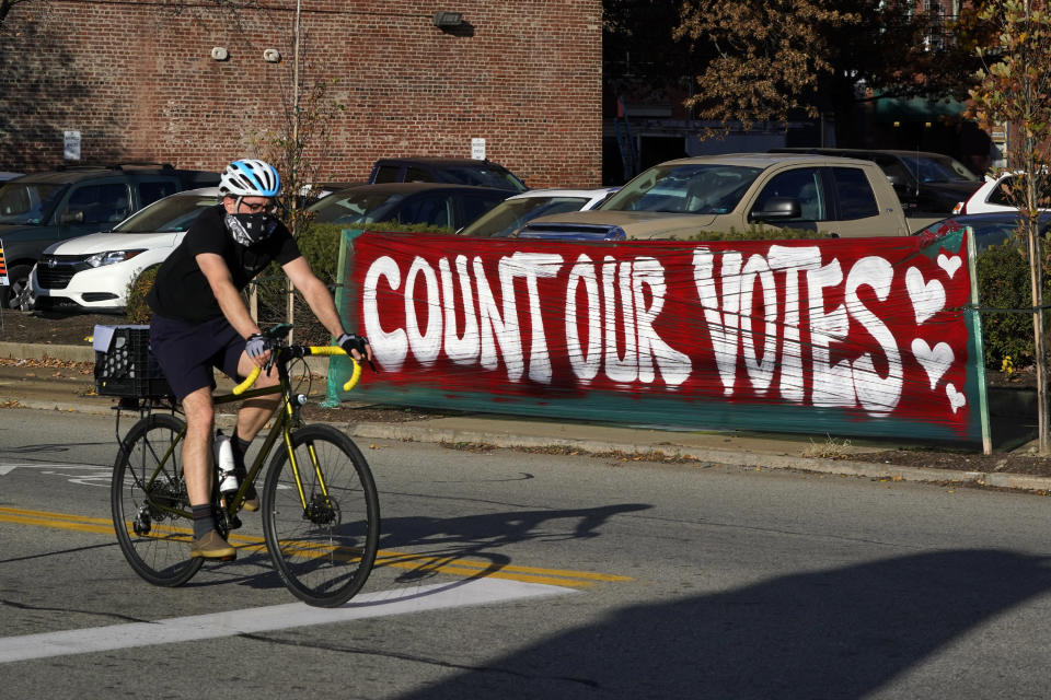 A bicyclist passes a Count Our Votes sign near the Allegheny County Election Division Warehouse on Pittsburgh's Northside where votes continue to be counted, Tuesday, Nov. 10, 2020. (AP Photo/Gene J. Puskar)