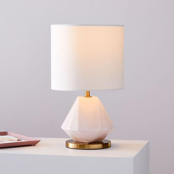 """If you're looking for something minimalist, this porcelain lamp just might catch your eye. This lamp features a faceted blush base, an """"Antique Brass"""" metal finish and a white linen shade. It is a plug-in, so you'll need a <a href=""""https://fave.co/32uZbGV"""" target=""""_blank"""" rel=""""noopener noreferrer"""">white LED bulb</a>.<a href=""""https://fave.co/32u7F14"""" target=""""_blank"""" rel=""""noopener noreferrer"""">Find it for $63 at West Elm</a>."""