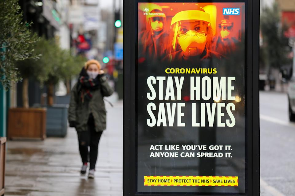 LONDON, UNITED KINGDOM - 2021/01/12: A woman walks past the Government's 'Stay Home, Save Lives' Covid-19 publicity campaign poster in London, as the number of cases of the mutated variant of the SARS-Cov-2 virus continues to spread around the country. (Photo by Dinendra Haria/SOPA Images/LightRocket via Getty Images)