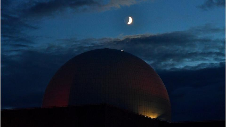 White domed nuclear power plant under a dark sky with crescent moon