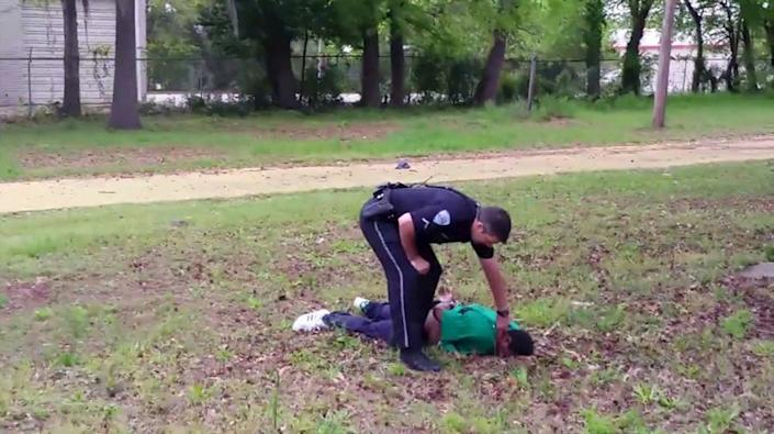 North Charleston police officer Michael Slager is seen standing over Walter Scott after allegedly shooting him in the back as he ran away in this still image from video. (Reuters/Handout)