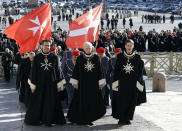 Members of the Knights of Malta walk in procession towards St. Peter's Basilica during a celebration to mark the 900th anniversary of the Order of the Knights of Malta, at the Vatican, Saturday, Feb. 9, 2013. The order traces its history to the 11th century with the establishment of an infirmary in Jerusalem that cared for people of all faiths making pilgrimages to the Holy Land. It is the last of the great lay chivalrous military orders like the Knights Templars that combined religious fervor with fierce military might to protect and expand Christendom from Islam's advance during the Crusades. In February 1113, Pope Paschal II issued a papal bull recognizing the order as independent from bishops or secular authorities, reason for Saturday's anniversary celebrations at the Vatican. (AP Photo/Gregorio Borgia)