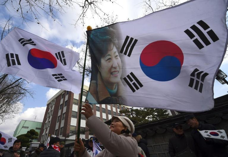 A pro-government activist waves a national flag showing a portrait of South Korea's President Park Geun-Hye during a rally opposing impeachment of the President near the Constitutional Court in Seoul on March 9, 2017