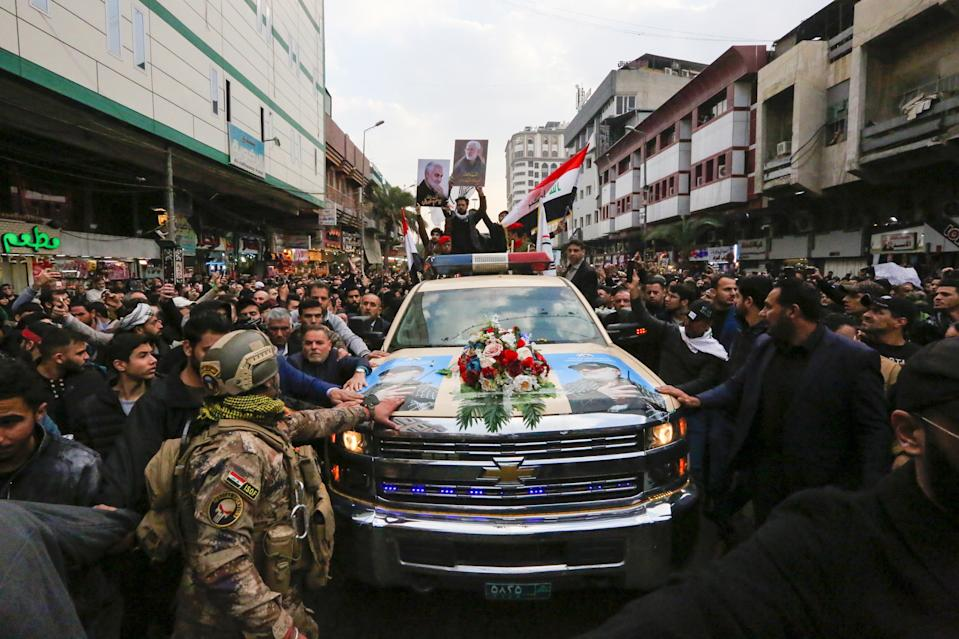 """Iraqis mourn over a coffin during the funeral procession of Iraqi paramilitary chief Abu Mahdi al-Muhandis and Iranian military commander Qasem Soleimani, and eight others, in Kadhimiya, a Shiite pilgrimage district of Baghdad, on January 4, 2020. - Thousands of Iraqis chanting """"Death to America"""" joined the funeral procession Saturday for Iranian commander Qassem Soleimani and Iraqi paramilitary chief Abu Mahdi al-Muhandis, both killed in a US air strike. The cortege set off around Kadhimiya, a Shiite pilgrimage district of Baghdad, before heading to the Green Zone government and diplomatic district where a state funeral was to be held attended by top dignitaries. In all, 10 people -- five Iraqis and five Iranians -- were killed in Friday morning's US strike on their motorcade just outside Baghdad airport. (Photo by SABAH ARAR / AFP) (Photo by SABAH ARAR/AFP via Getty Images)"""