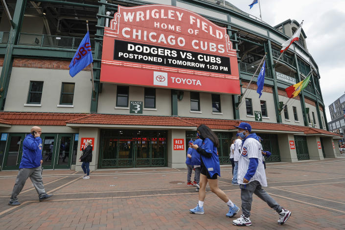 CORRECTS YEAR TO 2021 NOT 2020 - Fans walk outside Wrigley Field as a baseball game between the Chicago Cubs and the Los Angels Dodgers was postponed due to the forecast of inclement weather, Monday, May 3, 2021, in Chicago. (AP Photo/Kamil Krzaczynski)