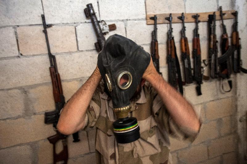 A rebel tries on a gas mask seized from a Syrian army factory in the north-western province of Idlib