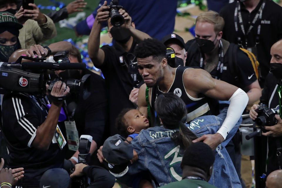 Milwaukee Bucks forward Giannis Antetokounmpo hugs his girlfriend Mariah Riddlesprigger and son Liam after defeating the Phoenix Suns in Game 6 of basketball's NBA Finals Tuesday, July 20, 2021, in Milwaukee. The Bucks won 105-98. (AP Photo/Aaron Gash)