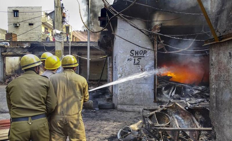Personnel try to douse fire in one of the shops in Gokulpuri areas in New Delhi. PTI
