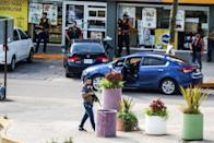 """Cartel gunmen are seen outside during clashes with federal forces following the detention of Ovidio Guzman, son of drug kingpin Joaquin """"El Chapo"""" Guzman, in Culiacan"""