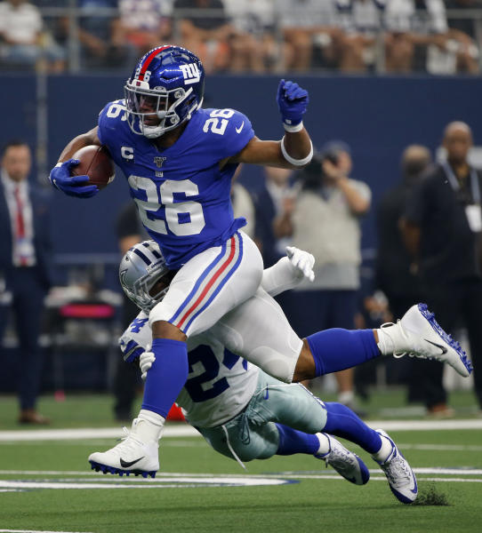 New York Giants running back Saquon Barkley (26) attempts to escape the tackle by Dallas Cowboys cornerback Chidobe Awuzie (24) in the first half of a NFL football game in Arlington, Texas, Sunday, Sept. 8, 2019. (AP Photo/Michael Ainsworth)