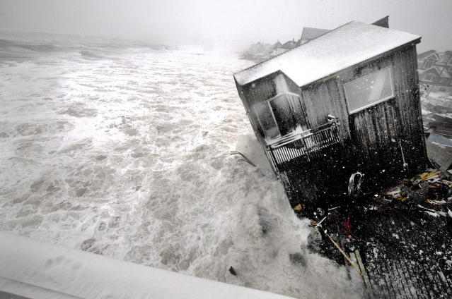 A house on the Plum Island seacoast in Newbury, Mass., sits partially collapsed into the churning surf, driven by winds from a slow-moving storm centered far out in the Atlantic Ocean, at high tide Friday morning, March 8, 2013. The storm dropped up to a foot of snow in some parts of New England, caused coastal flooding in Massachusetts and slowed the morning commute in the region to a slushy crawl. (AP Photo/Newburyport Daily News, Jim Vaiknoras)
