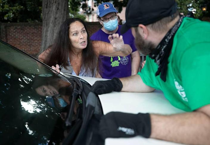 Deborrah Newton works remove a protester from the hood of her car at the intersection of Jones and Blount Streets on Thursday, July 2, 2020 in Raleigh, N.C, Five other protesters stopped the car initially next to the Executive Mansion, before Newton exited her car and tried to remove the man.