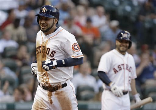 Houston Astros' Marwin Gonzalez, left, smiles as he heads to the dugout after scoring on a Jimmy Paredes double against the Los Angeles Angels in the third inning of a baseball game Wednesday, May 8, 2013, in Houston. Jose Altuve is at right. (AP Photo/Pat Sullivan)