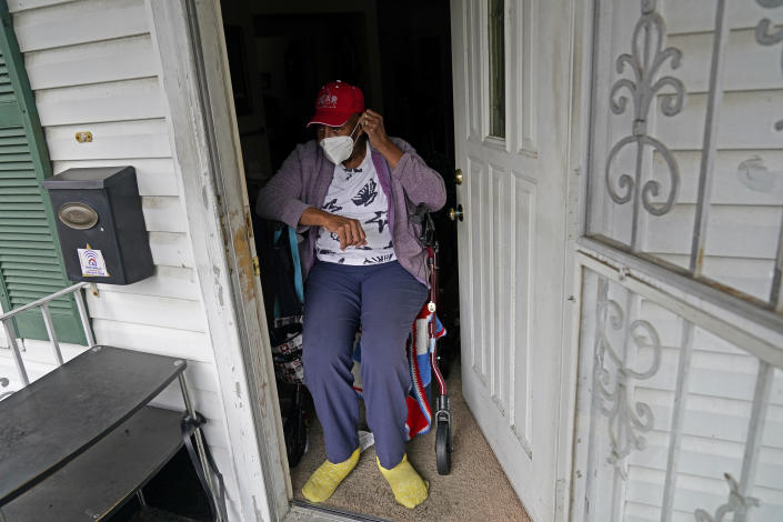 """Helen Green puts on her face mask as a box of meals is delivered by Revolution Foods in New Orleans on Thursday, Feb. 11, 2021. Green, 76, must use a walker to get around and depended on her 96-year-old mother to cook for both of them before the older woman fell and went to an assisted living facility. """"I'm very thankful for these meals. It makes a big difference in your life, you know,"""" she said. (AP Photo/Gerald Herbert)"""