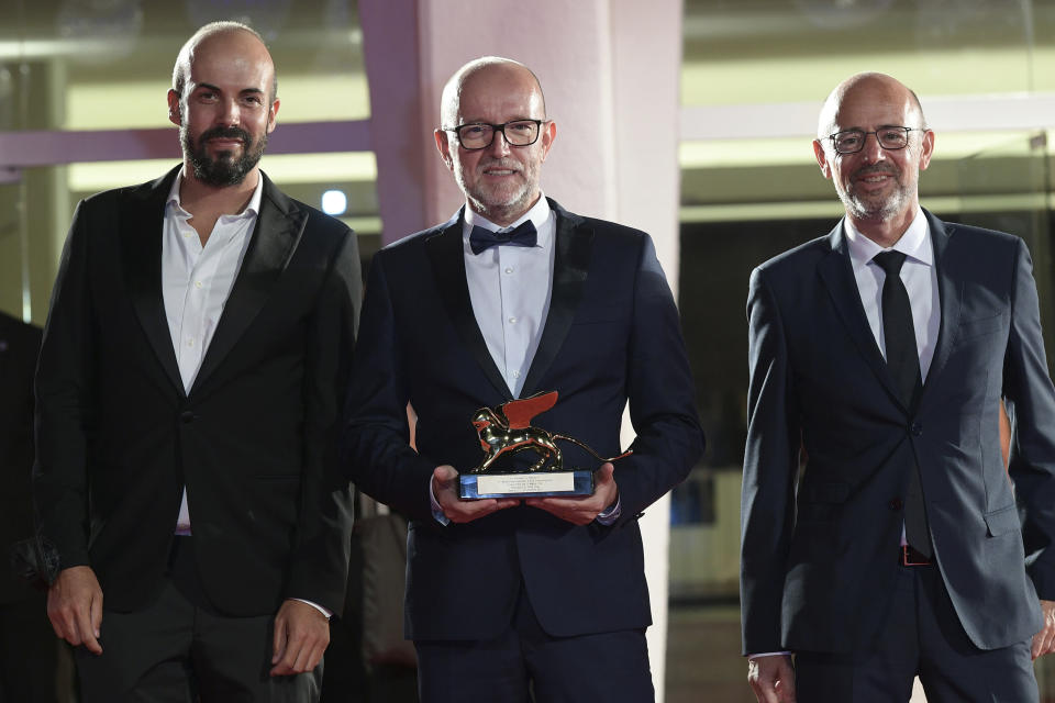 "Disney's Marketing Director for Italy, Davide Romani, center, holds the Golden Lion Best Film award for ""Nomadland"", at the closing ceremony of 77th edition of the Venice Film Festival, in Venice, Italy, Saturday Sept. 12, 2020. Director Chloe Zhao's ""Nomadland,"" a recession-era road trip drama starring Frances McDormand, has won the Golden Lion for best film at the Venice Film Festival, held against the backdrop of the coronavirus pandemic. (Gian Mattia D'Alberto/LaPresse via AP)"