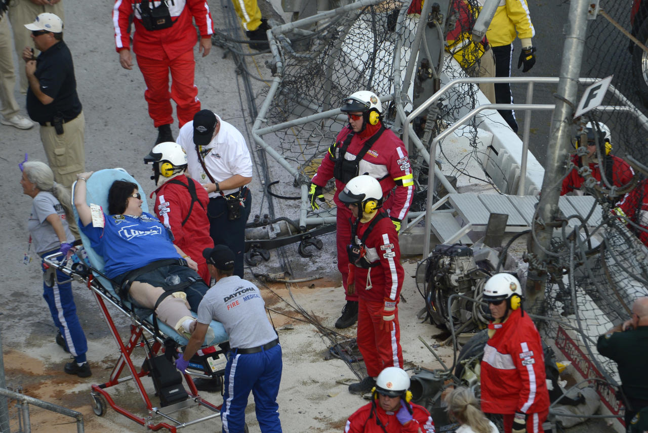 An injured spectator is transported by emergency personnel after a crash at the conclusion of the NASCAR Nationwide Series auto race Saturday, Feb. 23, 2013, at Daytona International Speedway in Daytona Beach, Fla. Driver Kyle Larson's car hit the safety fence sending car parts and other debris flying into the stands. Larson's engine lays on the right, inside the fence.(AP Photo/Phelan M. Ebenhack)