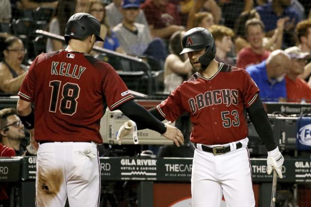 Arizona Diamondbacks' Carson Kelly (18) is greeted by Christian Walker (53) after scoring against the Philadelphia Phillies during the third inning of a baseball game Wednesday, Aug. 7, 2019, in Phoenix. (AP Photo/Ross D. Franklin)