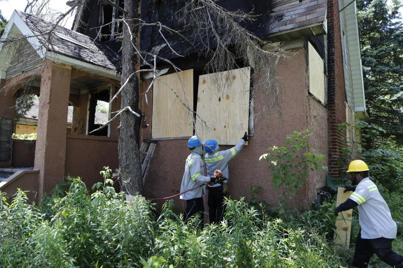 FILE - In this June 11, 2019 file photo, members of the Detroit's Board Up Brigade board up a vacant home in north Detroit. Murder charges could be announced against man suspected of killing at least four women and stowing their bodies in vacant houses in Detroit. Wayne County Prosecutor Kym Worthy is expected Wednesday, Sept. 18, to discuss the case against 34-year-old Deangelo Martin.(AP Photo/Carlos Osorio, File)