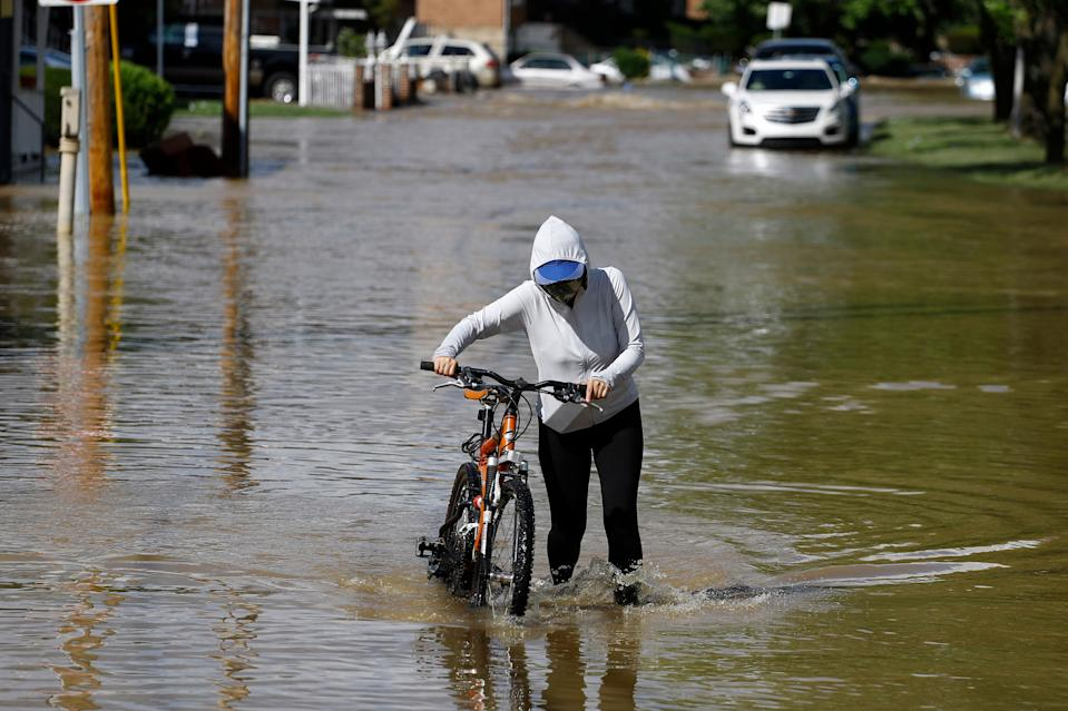 A woman pushes a bike through a flooded neighborhood during Tropical Storm Isaias in Philadelphia, Pennsylvania, August 4, 2020.