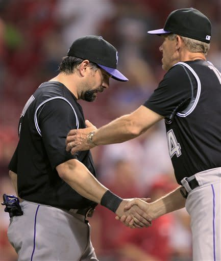 Colorado Rockies manager Jim Tracy (4) congratulates Todd Helton after the Rockies defeated the Cincinnati Reds 6-3 in a baseball game, Friday, May 25, 2012, in Cincinnati. Helton had a home run and three RBIs in the game. (AP Photo/Al Behrman)