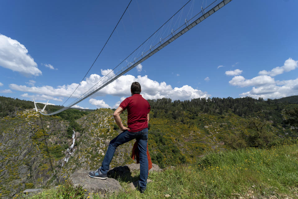 A man looks at a narrow footbridge suspended across a river canyon, which claims to be the world's longest pedestrian bridge, in Arouca, northern Portugal, Sunday, May 2, 2021. The Arouca Bridge inaugurated Sunday, offers a half-kilometer (almost 1,700-foot) walk across its span, some 175 meters (574 feet) above the River Paiva. (AP Photo/Sergio Azenha)