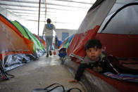 In this March 12, 2019, image, 10-month-old Joshua Perla looks out from the family's tent in a shelter for migrants in Tijuana, Mexico. Asylum seekers are now forced to wait in Mexico while their cases wind through U.S. immigration courts. They often struggle to find legal advice and say they feel unsafe. The Trump administration introduced the new policy in January amid a surge of asylum-seeking families from Guatemala, Honduras and El Salvador arriving at the Mexican border. (AP Photo/Gregory Bull)