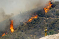 A firefighter watches a 1,400-acre wildfire northeast of Castaic, Calif., Friday May 31, 2013. Crews battling this wildfire in the mountains north of Los Angeles took advantage of cool morning weather Friday to make progress but scattered flames continued to climb hillsides. A flare-up prompted Los Angeles County sheriff's deputies to briefly evacuate about 25 homes along a canyon road in the Angeles National Forest Friday morning but residents were later allowed to return. (AP Photo/Nick Ut)