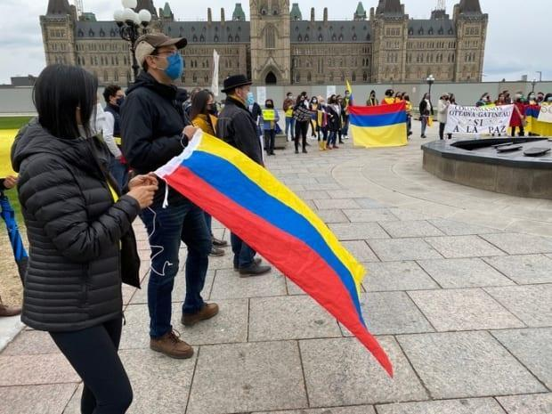 Members of Ottawa-Gatineau's Colombian community wear masks as they rally against police repression in their homeland at a Friday protest on Parliament Hill.