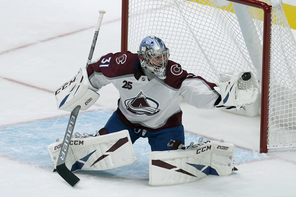 Colorado Avalanche goaltender Philipp Grubauer catches the puck on a shot by the San Jose Sharks during the third period of an NHL hockey game in San Jose, Calif., Wednesday, March 3, 2021. (AP Photo/Jeff Chiu)