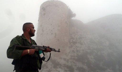 "A member of the Free Syrian Army stands near the  ""Al-Hosn"" Crusaders Citadel on the outskirts of Homs"