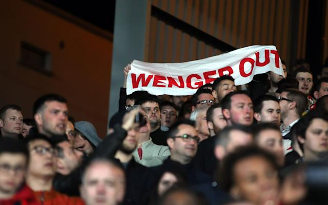 Arsenal fans hold up a banner in protest against manager Arsene Wenger Credit: PA