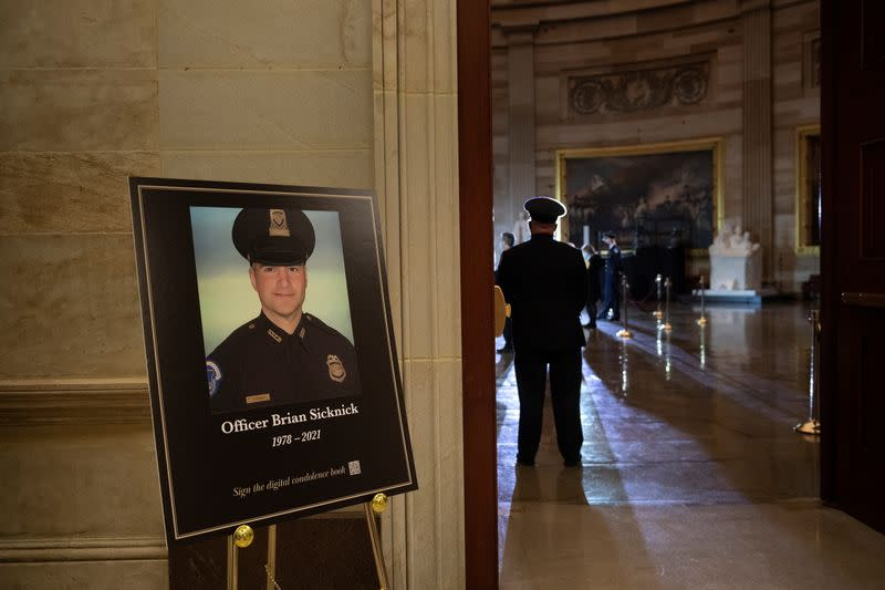 A picture of of Capitol Police officer Brian Sicknick is seen as people wait for his remains to arrive to lay in honor in the Rotunda of the U.S. Capitol building in Washington