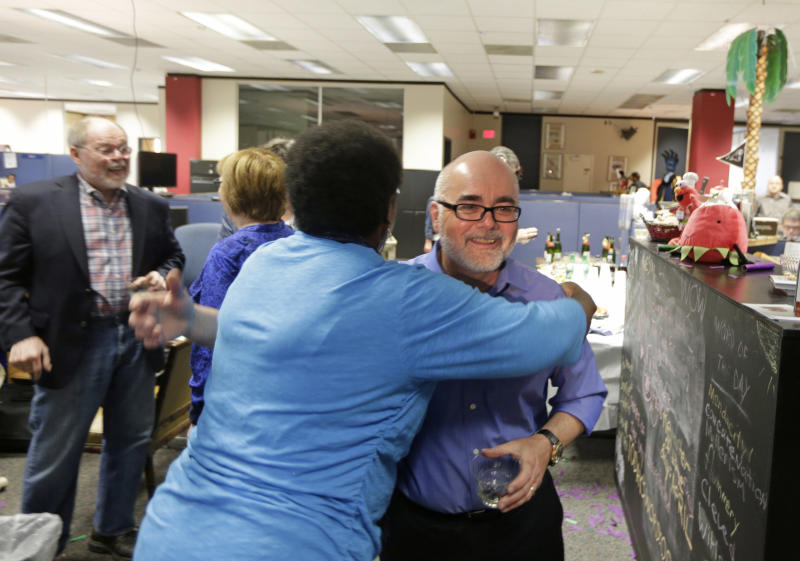 Charlotte Observer editorial cartoonist Kevin Siers, right, gets a hug from a co-worker as the newsroom celebrates Siers winning the Pulitzer Prize for Editorial Cartooning at the newspaper in Charlotte, N.C., Monday, April 14, 2014. (AP Photo/Chuck Burton)