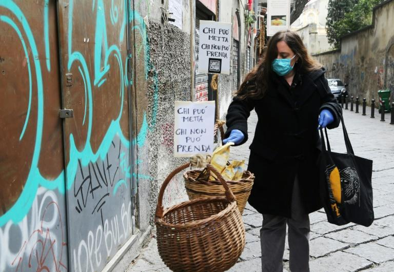 "A woman puts food in a solidarity basket displayed with a note reading, ""Who can put, who cannot take"" in Naples, as Italy sees evidence it may have made it through the worst of the coronavirus pandemic"