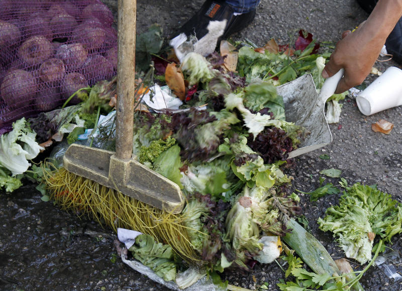 A man sweeps discarded salad vegetables from the floor at a food market in Vienna, Austria, on Monday May 30, 2011.  Vegetables from Spain are suspected of carrying the dangerous E.coli bacteria, which is suspected of killing some people in Germany and has caused many hundreds of people to become ill across Europe.  Austria has moved to ban the sale of cucumbers, tomatoes and eggplants that originated from Spain, although Spanish authorities said there is no proof that they are the source of the outbreak.(AP Photo/Ronald Zak)