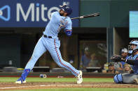 Texas Rangers Joey Gallo (13) follows through on a solo home run in the sixth inning against the Minnesota Twins in a baseball game Sunday, June 20, 2021, in Arlington, Texas. (AP Photo/Richard W. Rodriguez)