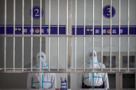 Security officers in protective suits stand at a reception area at the visitors' hall at the Urumqi No. 3 Detention Center in Dabancheng in western China's Xinjiang Uyghur Autonomous Region, on April 23, 2021. Urumqi No. 3, China's largest detention center, is twice the size of Vatican City and has room for at least 10,000 inmates. (AP Photo/Mark Schiefelbein)