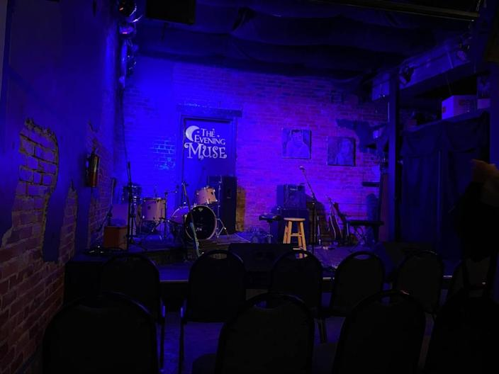 The stage is set for performers, and chairs await a full crowd at The Evening Muse.