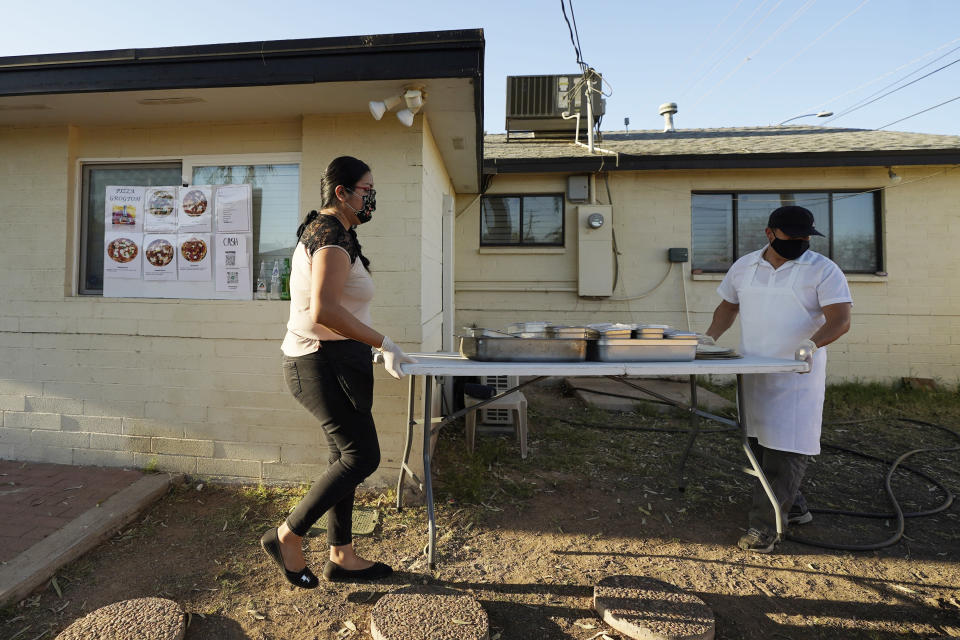 Ruby Salgado, left, and chef Jose Hernandez set up their pizza making station in the backyard of their home in Scottsdale, Ariz. on April 3, 2021. Beaten down by the pandemic, some laid-off or idle restaurant workers have pivoted to dishing out food from home. (AP Photo/Ross D. Franklin)