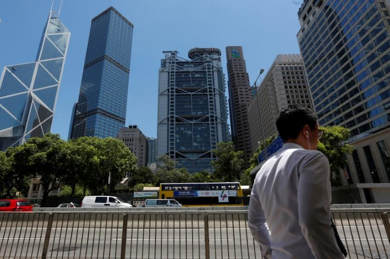 A man walks in front of the Bank of China Tower, Cheung Kong Center, HSBC bank and Standard Chartered bank at the financial central district in Hong Kong