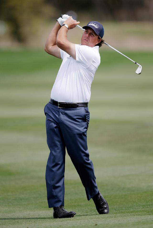 Phil Mickelson watches his fairway shot on the 14th hole during the third round of the Texas Open golf tournament, Saturday, March 29, 2014, in San Antonio. Mickelson withdrew from the tournament with a pulled muscle. (AP Photo/Eric Gay)