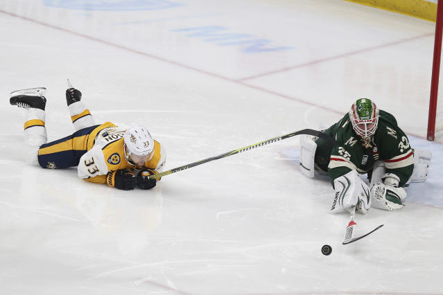 Minnesota Wild goalie Alex Stalock reaches out to block the puck as Nashville Predators' Viktor Arvidsson of Sweden slides across the ice during the third period of an NHL hockey game Sunday, March 3, 2019, in St. Paul, Minn. The Predators won 3-2 in a shootout. (AP Photo/Stacy Bengs)