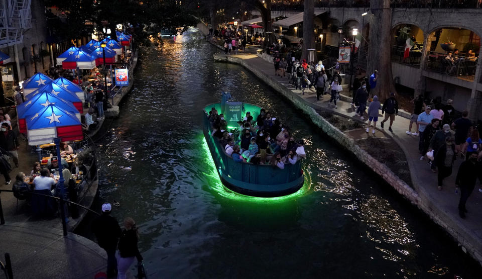 Visitors crowd the River Walk in San Antonio, Thursday, March 18, 2021, as the city prepares to host the Women's NCAA College Basketball Championship. (AP Photo/Eric Gay)