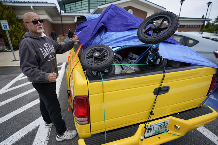 Roy Alicea, of Salem, N.H., checks the tie-down straps securing his gear during a stop at a rest area on the Maine Turnpike, Friday, May 28, 2021, in Kennebunk, Maine. Alicea was headed to a campground in Steep Falls, Maine. (AP Photo/Robert F. Bukaty)