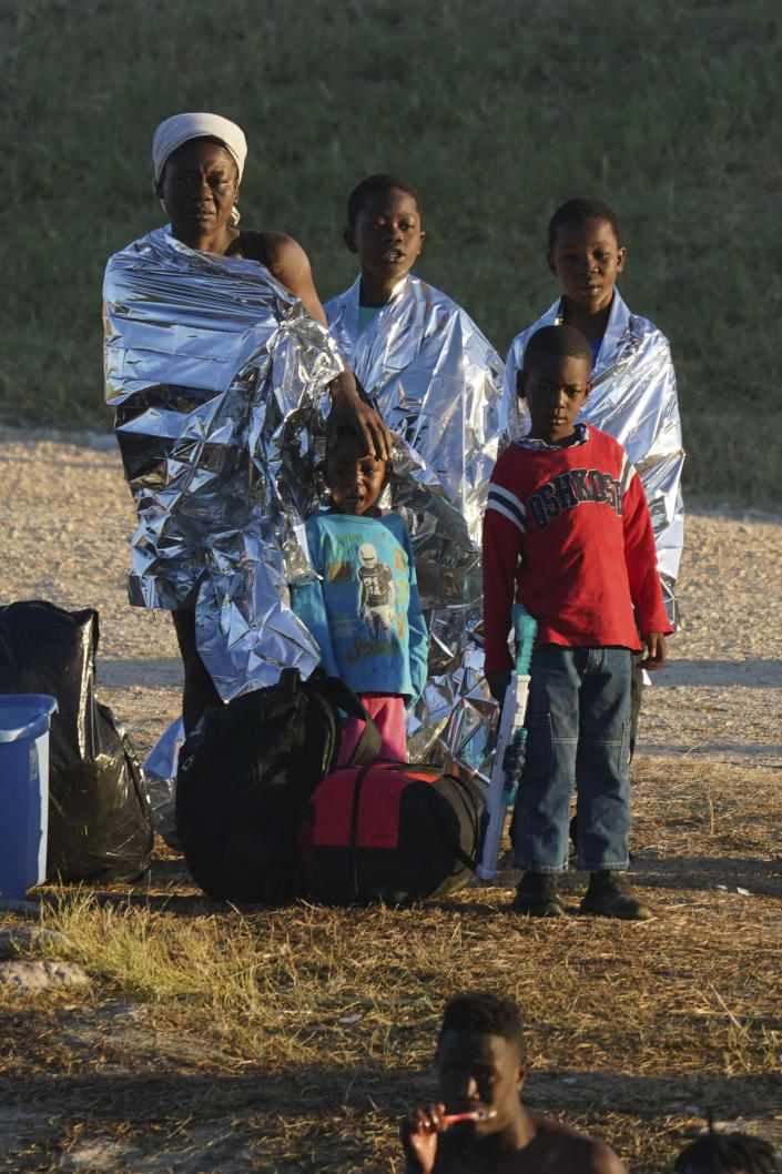 A migrant family stands on the U.S. side of the Rio Grande river where another migrant brushes his teeth, after they crossed the border to Del Rio, Texas, from Ciudad Acuna, Mexico, early Thursday, Sept. 23, 2021. (AP Photo/Fernando Llano)