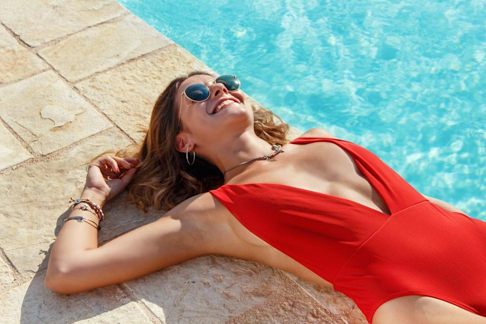 Best One-Piece Swimsuits , Young caucasian woman in red swimsuit relaxing near a pool