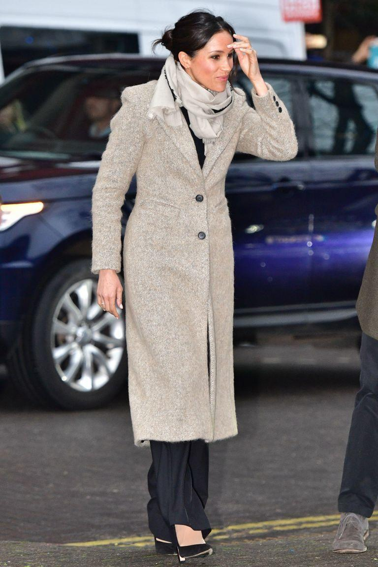 """<p>Markle wore a <a href=""""http://www.revolve.com/smythe-brando-coat-in-camel/dp/SMYT-WO124/?source=ran&ranMID=41816&ranEAID=TnL5HPStwNw&ranSiteID=TnL5HPStwNw-iE1yQjnfbURoiVBUBmGQwg"""" rel=""""nofollow noopener"""" target=""""_blank"""" data-ylk=""""slk:Smythe 'Brando coat'"""" class=""""link rapid-noclick-resp"""">Smythe 'Brando coat'</a>, a Marks and Spencer wool blend <a class=""""link rapid-noclick-resp"""" href=""""http://www.marksandspencer.com/wool-blend-round-neck-bell-sleeve-jumper/p/p22511692?OmnitureRedirect=T385065T&source=affwindow&extid=af_a_Content_78888_Skimlinks&comgp=78888&cvosrc=affiliate.aw.78888&awc=1402_1515583060_4361ef0778021488b92633238c559529"""" rel=""""nofollow noopener"""" target=""""_blank"""" data-ylk=""""slk:round neck bell sleeve"""">round neck bell sleeve </a><a class=""""link rapid-noclick-resp"""" href=""""http://www.marksandspencer.com/wool-blend-round-neck-bell-sleeve-jumper/p/p22511692?OmnitureRedirect=T385065T&source=affwindow&extid=af_a_Content_78888_Skimlinks&comgp=78888&cvosrc=affiliate.aw.78888&awc=1402_1515583060_4361ef0778021488b92633238c559529"""" rel=""""nofollow noopener"""" target=""""_blank"""" data-ylk=""""slk:jumper"""">jumper</a>, <a href=""""https://uk.burberry.com/wool-wide-leg-trousers-p40582801"""" rel=""""nofollow noopener"""" target=""""_blank"""" data-ylk=""""slk:Burberry trousers"""" class=""""link rapid-noclick-resp"""">Burberry trousers</a> and a scarf by Jigsaw. </p><p>She accessorised the look with a <a href=""""https://zofiaday.myshopify.com/collections/rings/products/bar-stack-rings?variant=44138586115"""" rel=""""nofollow noopener"""" target=""""_blank"""" data-ylk=""""slk:Bar Stack Ring"""" class=""""link rapid-noclick-resp"""">Bar Stack Ring</a> in 14-karat yellow gold featuring pavé diamonds from Zofia Day to visit a Radio station in Brixton.<br></p>"""
