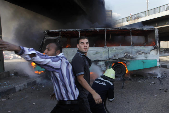 """An Egyptian calls for help to extinguish a fire reported to be set by black block protesters on a bus belonging to Muslim Brotherhood supporters in Cairo, Egypt, Friday, April 19, 2013. Several hundred supporters and opponents of Egypt's President Mohammed Morsi clashed near Cairo's Tahrir Square amid a rally calling on Morsi to """"cleanse the judiciary.""""(AP Photo/Amr Nabil)"""