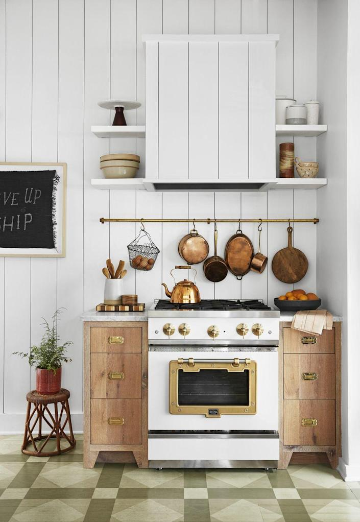 """<p>A white-and-brass range is classic yet eye-catching, like jewelry for this kitchen. """"Black would have been too stark and stainless wouldn't have been right with all the brass accents,"""" the homeowner says. Stacks of simple wood drawers on either side of the range and other mixed metal accessories really warm up the crisp, white paneled walls.</p>"""